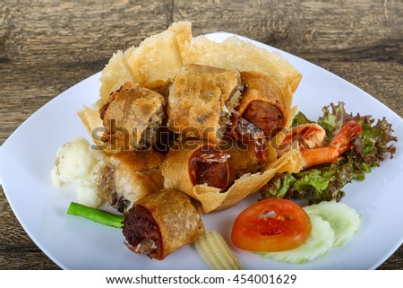 Fried spring rolls in eatable basket with salad leaves #454001629