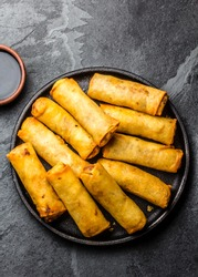 Fried spring rolls on black iron plate on grey stone slate background. Top view