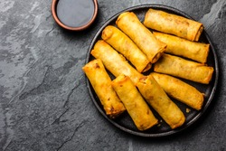 Fried spring rolls on black iron plate on grey stone slate background. Top view, copy space