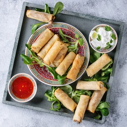 Fried spring rolls with red and white sauces, served in china plate on square wood tray with fresh green salad over gray blue texture background. Flat lay, space. Asian food. Square image