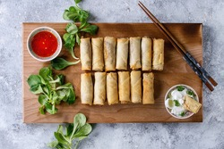 Fried spring rolls with red and white sauces, served on wood serving board with fresh green salad and wooden chopsticks over gray blue texture background. Flat lay, space. Asian food