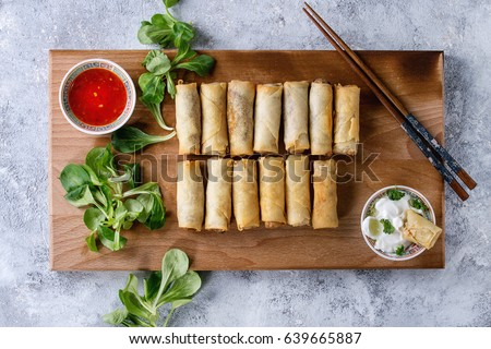 Fried spring rolls with red and white sauces, served on wood serving board with fresh green salad and wooden chopsticks over gray blue texture background. Flat lay, space. Asian food #639665887