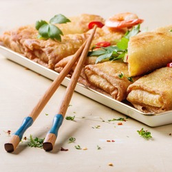 Fried spring rolls with vegetables and shrimps, served with spicy sauce and chopsticks over white wooden background. Square image with selective focus