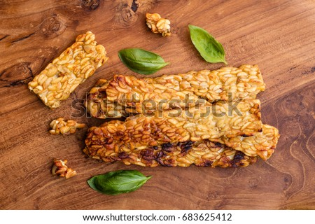 Fried tempeh decorated with basil leaves on wooden surface. Top view