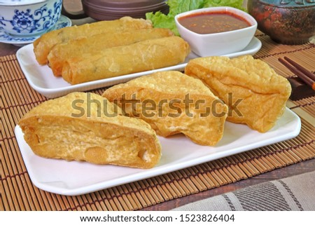 Fried Tofu and Deep fried crispy Spring rolls, served with sweet and spicy chili sauce. Vegetarian food for Vegetarian festival. Selective focus