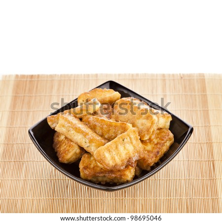 fried tofu, soy products on black plate bowl isolated on white background