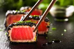 Fried tuna steak in black sesame with chopsticks