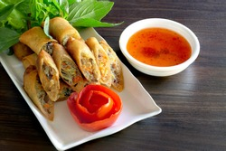 Fried Veg. spring rolls in white dish with vegetables on the dark wooden background / Selective focus image