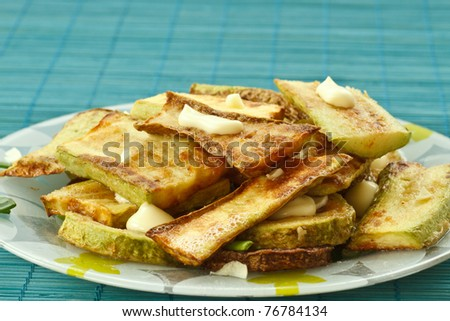 fried zucchini with garlic closeup on a plate - stock photo