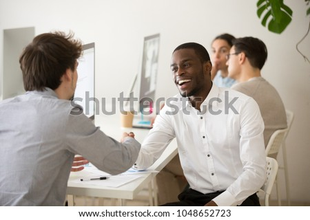 Friendly african advisor handshaking customer or colleague in office, smiling black and white entrepreneurs happy to make deal, excited diverse colleagues shake hands celebrating successful teamwork