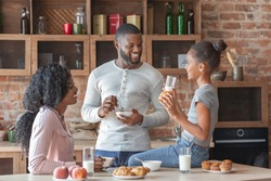Friendly african american family of three talking at kitchen during breakfast, free space