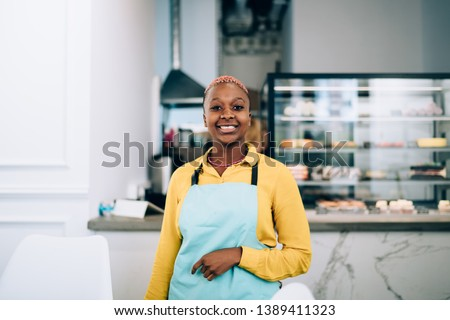 Friendly African American female in apron cheerfully smiling and looking at camera while working as waitress in modern cozy cafe