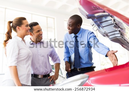friendly african american vehicle dealer showing couple new car engine