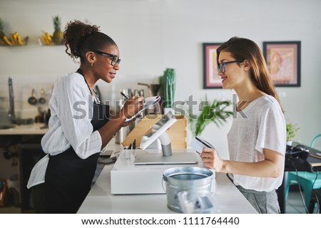 friendly african american waitress taking order on notepad from customer