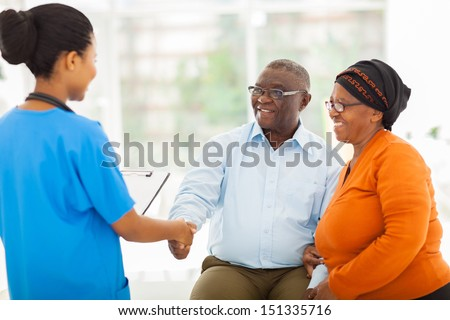 friendly african female nurse greeting senior couple in hospital