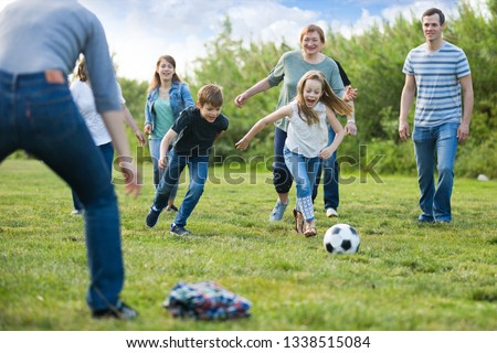 Friendly and glad family playing football and scoring goals #1338515084