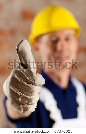 Friendly and reliable construction worker giving thumbs up, focus on thumb