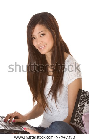 Friendly Asian High school girl student sitting in jeans with portable laptop PC computer