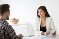 Friendly asian hr smiling laughing talking to candidate at job interview, chinese financial advisor explains customer deal benefit, happy korean businesswoman bank worker consulting client about loan