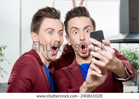 Friendly brothers twins having fun taking selfie photo with smart phone in the white home or restaurant interior