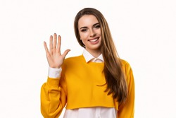 Friendly brunette girl in casual clothes is saying hello, smiling joyfully and friendly, waving her hand, showing five fingers. Studio shot, white background