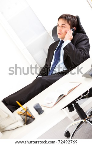 Friendly  business man sitting in office with feet on desk and talking on mobile phone