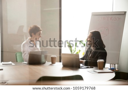 Friendly businessman and businesswoman enjoy conversation in meeting room, smiling happy partners or coworkers talking discussing new project idea, good relations at work concept, view through glass