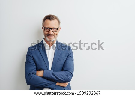 Friendly businessman wearing glasses and a suit posing with folded arms smiling at the camera against a white studio background with copy space