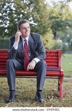 Friendly businessman with cell phone sitting on a red bench in a park