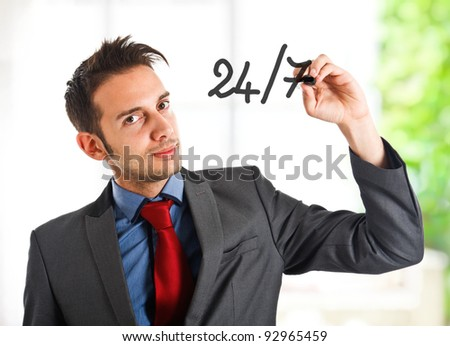 Friendly businessman writing 24/7 on the screen
