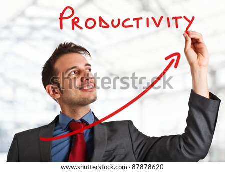 Friendly businessman writing the word Productivity and a rising arrow - stock photo
