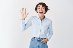 Friendly cheerful girl saying hello, raising hand and waiving at camera in greeting gesture, smiling upbeat, standing on white background.