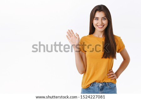 Friendly cheerful, happy smiling woman waving you with raised hand. Attractive girl greeting friend, say hello or hi, welcome guest, standing white background joyful, express positivity and joy