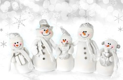 Friendly Christmas snowman family on a snow background.