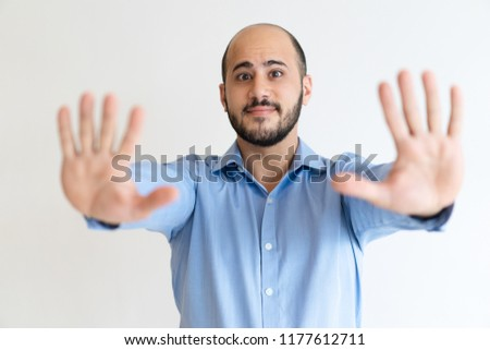 Friendly concerned office worker gesturing stop. Bald bearded Caucasian man in formal shirt showing both palms in handstop sign. Gesturing and warning concept
