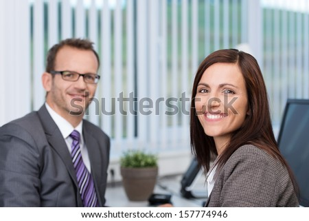 Friendly confident businesswoman with a lovely motivated smile sitting in her office with a male colleague
