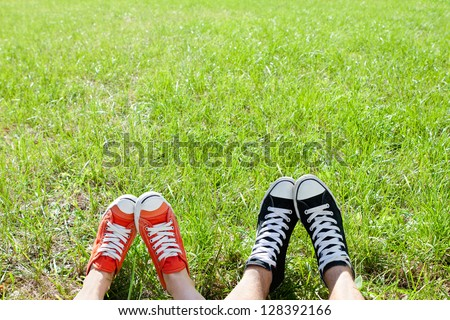 Friendly couple in sneackers in green grass #128392166