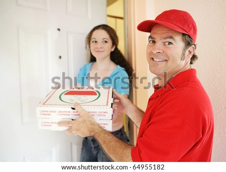 Friendly delivery man handing pizza to a customer.