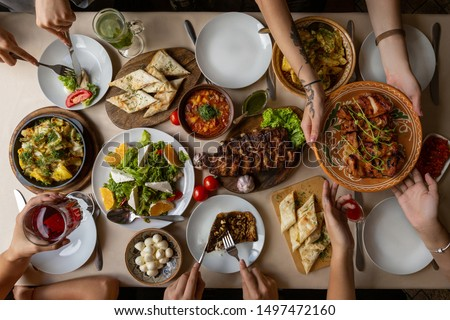 Friendly dinner. Top view of group of people having dinner together while sitting at the rustic wooden table with many plate of delicious and satisfying meals