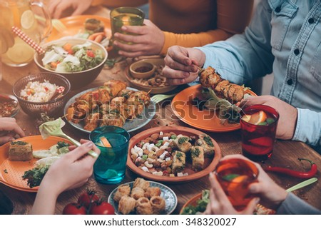 Friendly dinner. Top view of group of people having dinner together while sitting at the rustic wooden table - Shutterstock ID 348320027