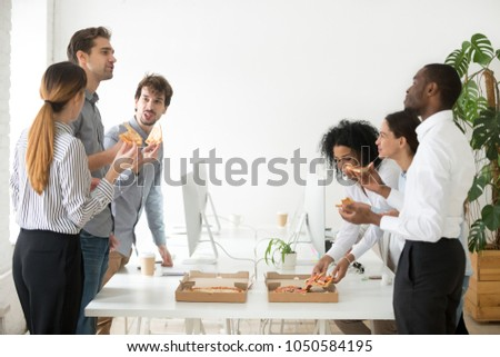 Friendly diverse business team members or multi-ethnic colleagues eating sharing pizza together in office, multiracial coworkers staff group enjoying break talking laughing on lunch time at meeting