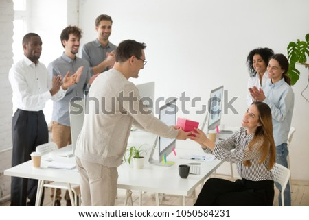 Friendly diverse corporate team congratulating happy female colleague with birthday and applauding, male employee presenting gift box greeting woman making pleasant surprise to coworker in office