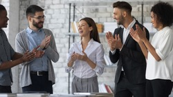Friendly diverse employees congratulating businesswoman with business achievement, great work results or job promotion, business people applauding and cheering, standing in modern office