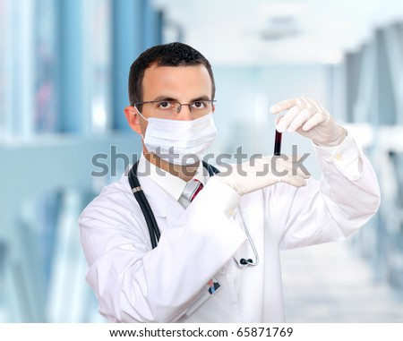 Friendly doctor -intern resarch a medical test glass with blood .