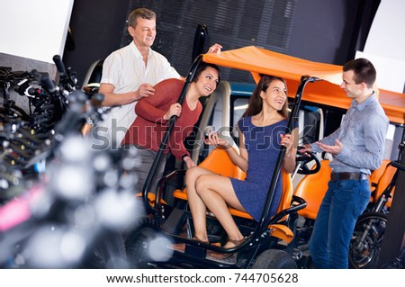 Friendly efficient kindly male employee helping family to select tour electrics at rental agency
