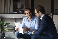 Friendly elder male employee mentor leader explaining paperwork to younger newbie colleague intern in modern office space, capable millennial lawyer assistant convincing customer in profits of deal