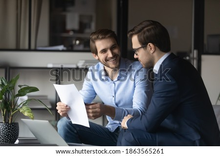 Friendly elder male employee mentor leader explaining paperwork to younger newbie colleague intern in modern office space, capable millennial lawyer assistant convincing customer in profits of deal Foto stock ©