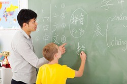 friendly elementary school teacher helping young boy writing chinese on chalkboard