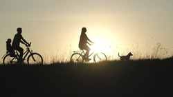 Friendly family with a child on bicycles during sunset.