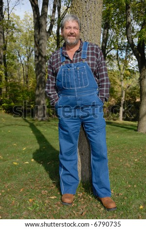 friendly farmer in blue bib overalls, in meadow, late afternoon,vertical